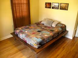 Queen Reclaimed Wood Bed Without Headboard Ausing Assorted Color Quilt  Added Gray Velvet Cushion On Brown bedroom ...
