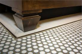 penny round floor tile with metal accent strip around marble border tile and custom vanity with