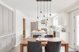 open plan dining room boasts a stained oak dining table illuminated by linear staggered glass lights and surrounded by charcoal gray slipcovered dining