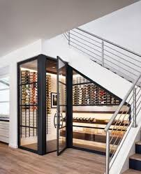 a cool modern under stairs wine cellar with lots of bottles on wall mounted shelves