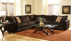 dark sectional couches with glass coffee table and cozy carpet tiles for traditional living room design