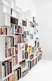 Large white shelving system with many books photographed angularly