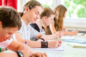 Students Or Pupils Of School Class Writing An Exam Test In