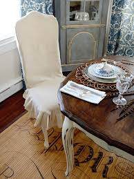 slipcovers are a great way to disguise mismatched seating or give dated chairs a quick update this dining room chair is covered in a white linen slipcover