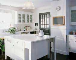 lovely white cottage kitchen with off white walls paired with chair rail and white beadboard