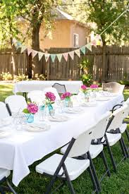 A backyard birthday dinner party using pink hydrangeas, blue canning jars,  and polka dots.
