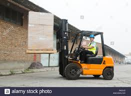Warehouse Worker Driving Forklift Loading And Unloading Cargo Stock
