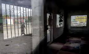a man is seen through a window reflection as he walks by an empty building on