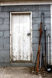 old shed door with metal stakes leaning next to it