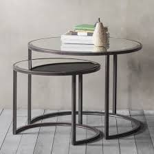 set of two round nesting tables with mirrored tops and crescent shaped metal bases