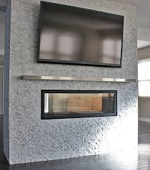 silver steel mantel shelf over rectangle fireplace with glass cover on grey stone wall