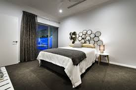 bedside tables bedroom layout with recessed lighting and white bed cover and grey blanket