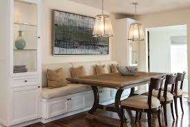 tall dining room table sets a built in banquette is flanked by tall gl cabinets for