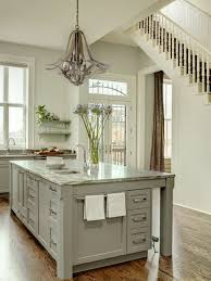 gray kitchen features gray chandelier over gray kitchen island topped with white and gray countertop and square prep sink over chocolate brown oak wood