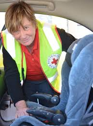 secure australian red cross volunteer teresa o nion checks a child s booster seat for