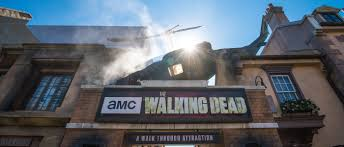 the sign for the walking dead attraction with a broken down helicopter on top