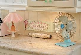 marble countertop with mini table lamp and small fan with chocolate priint paint image