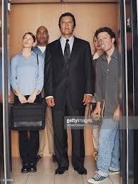 people standing in elevator. businessman standing in an elevator surrounded by a variety of people : stock photo i