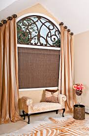 An arched window dressed in a beautiful angled panels, finished with a  custom faux iron  Curtains For Arched WindowsHanging CurtainsArch Windows Bedroom ...