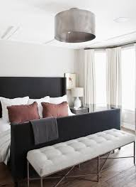 bedroom bench. contemporary bedroom features a metal drum semi flush mount light illuminating black wingback bed with bench