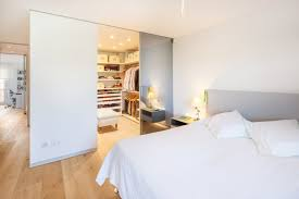 big walk in closet light coloured floor bed pillows clothes ceiling lights cool lamp shelves contemporary