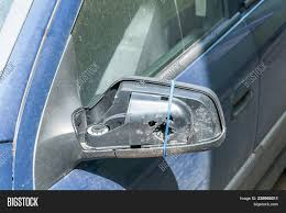 broken and damaged side mirror on the blue car doors with remaining wires holding plastic frame