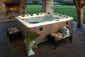 this above ground hot tub is placed on a stone patio and overlooks an open air above ground pools spa