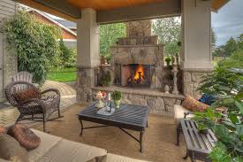 chic wicker rocking chair in patio traditional with small outdoor fireplace