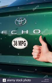 Close up of person holding thumbs up next to 38 miles per gallon ...
