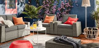 grey rattan outdoor sofas on a terrace with orange and red cushions