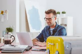 your home office. Man Wearing Jeans Shirt And Glasses Sitting At The Table In A Home Office, Working Your Office
