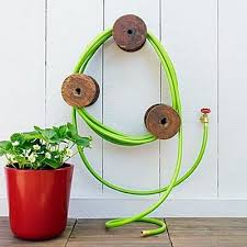 garden hose container. use old wooden spools (big ones) to make a garden hose holder container