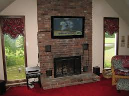 entertainment room with brick fireplace under wall mount tv stand among two glass window with maroon fl roman shade as well as mounting a tv to brick