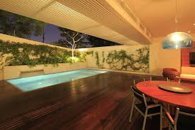 Modern Residential House Idea with Semi Indoor Lap Pool and Wooden Deck and  Round Shaped Dining