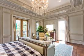 large luxury master bedroom with chandelier hardwood flooring access to patio and sofa