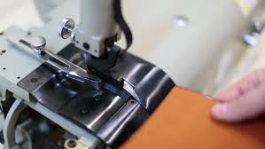 man works on leather skiving machine use to bevel the edges and to split strips of leather to various thicknesses for special s