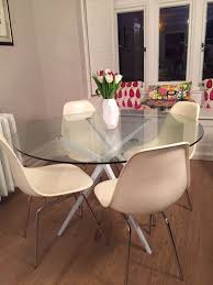 contemporary round glass table with 4 eames inspired white chairs