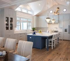 burnham design gorgeous coastal kitchen features light grey cabinets painted pratt lambert marble vein paired with white quartz countertops and white
