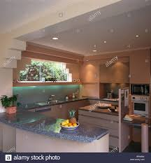 kitchen down lighting. grey granite worktop on peninsular unit in modern pink kitchen extension with downlighting above down lighting o