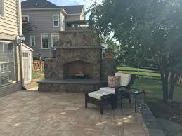 an outdoor stone fireplace on a hanover paver patio in leesburg va