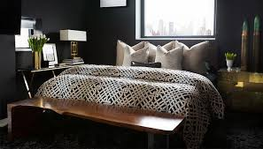 features walls painted black framing a square window over a black headboard on bed dressed in gray linen shams and a duvet in kelly wearstler ombre maze