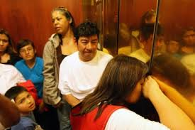 people stuck in elevator. a woman tries to breathe fresh air through crack in the doors when homeowners and people stuck elevator