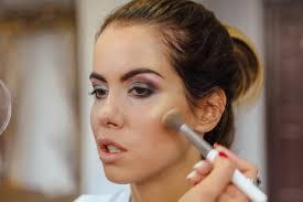 make up artist doing make up to the model in studio