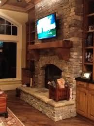 i like the rough wood mantel and the tv mounted over the fire place