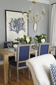 stunning dining room with visual fort lighting 6 light marigot chandelier in antique burnished br over rectangular dining table lined with navy blue