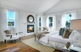 Beautiful White Master Bedroom With Fireplace And Wood Flooring