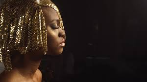 side view of magic surreal golden african american female model with bright glitter makeup and glossy golden hairstyle black studio background stock video