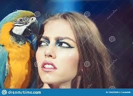 woman with blue and yellow macaw with makeup and bird pet beauty model with exotic ara friends and friendship