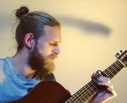 a blond guy with a man bun hairstyle and long hair playing with his guitar