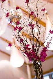 glass cylinder with curly willow (a rustic touch for Todd?) with orchids -  a few sprays at the top of the vase and a few blossoms attached to the  branches.